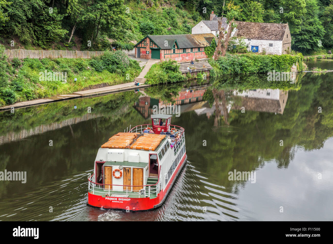 Pleasure boat on the River Wear in Durham turns as it reaches the weir taken from Prebends Bridge Stock Photo