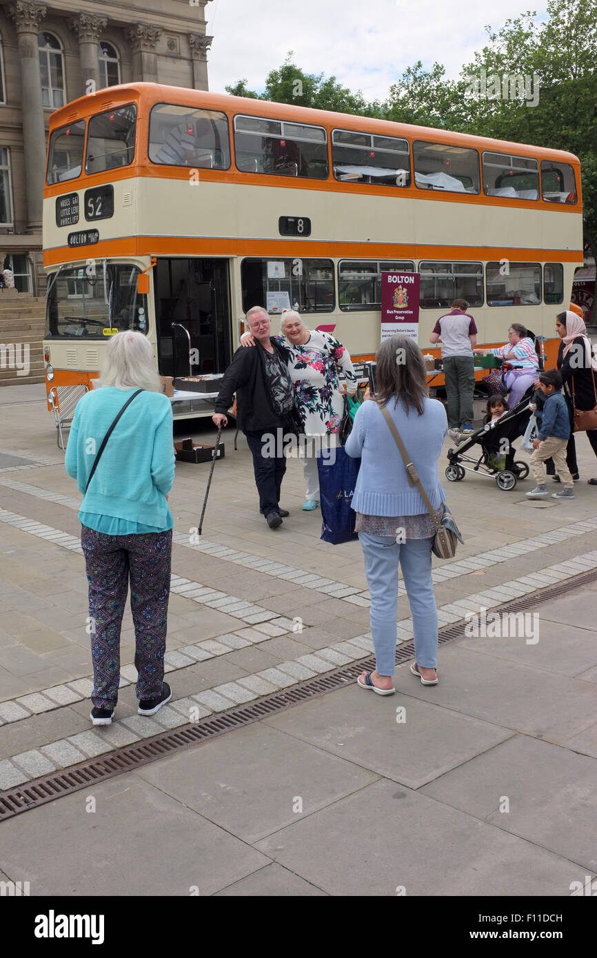 An elderly couple pose for a photo at a Bolton Bus Preservation Group fund raising event in Victoria Square, Bolton, - Stock Image