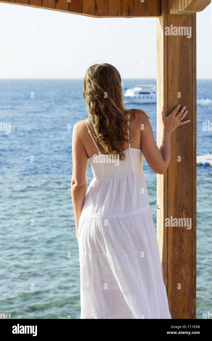 94a122bbf68e Young woman in white dress watching ship on the sea. Standing girl looking  at the ocean