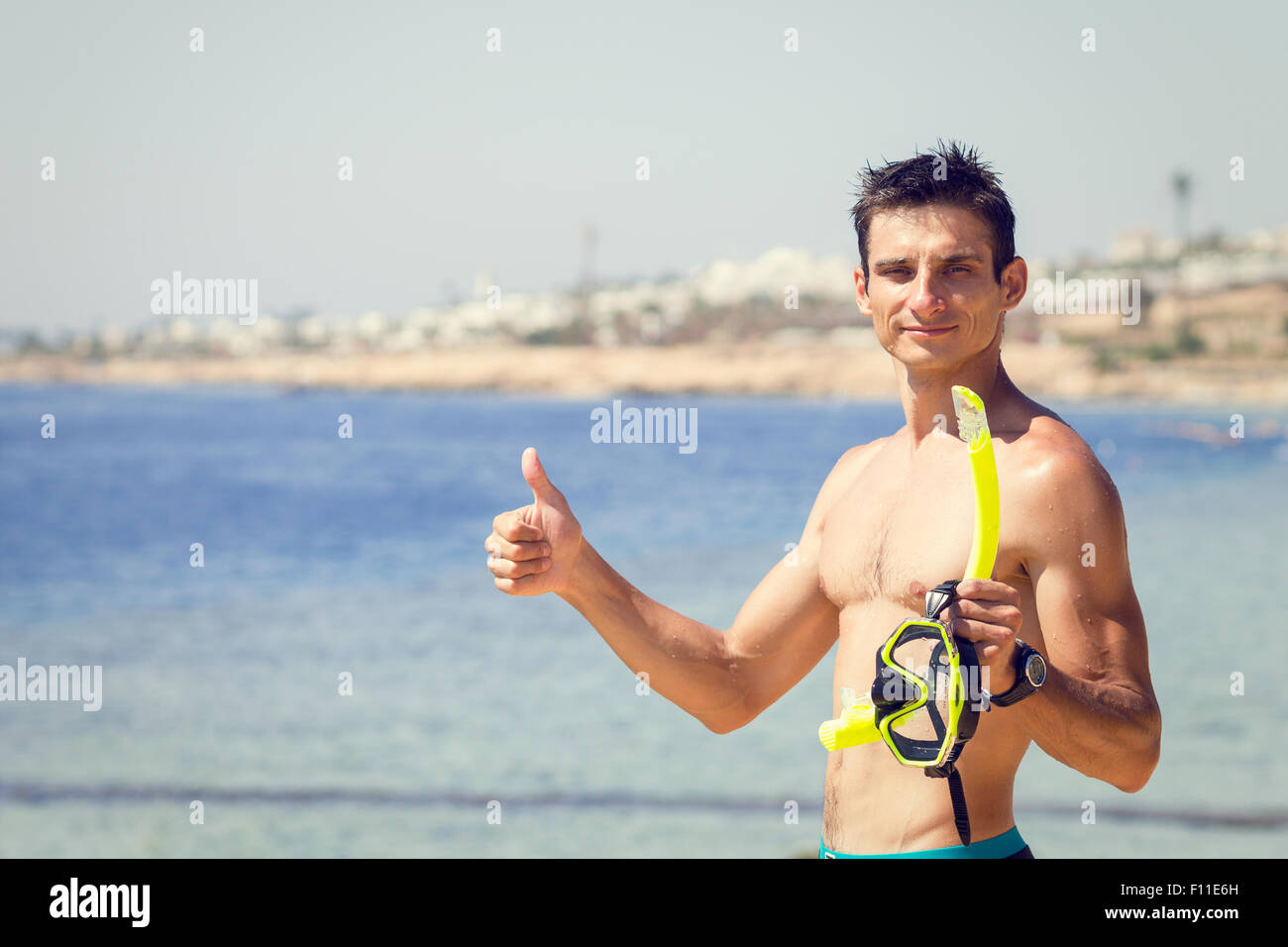Young man with mask and snorkel shows thumbs up at the sea beach. Summer vacation and snorkeling background with - Stock Image