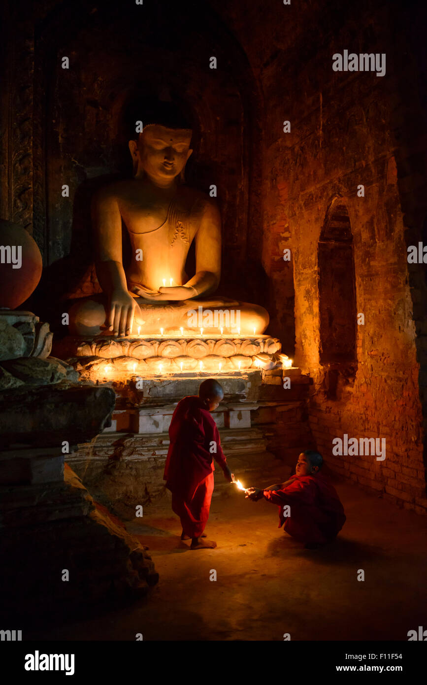 Asian monks-in-training lighting candles at Buddha shrine - Stock Image
