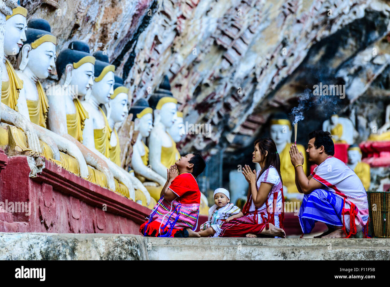 Asian family praying at Buddha temple - Stock Image