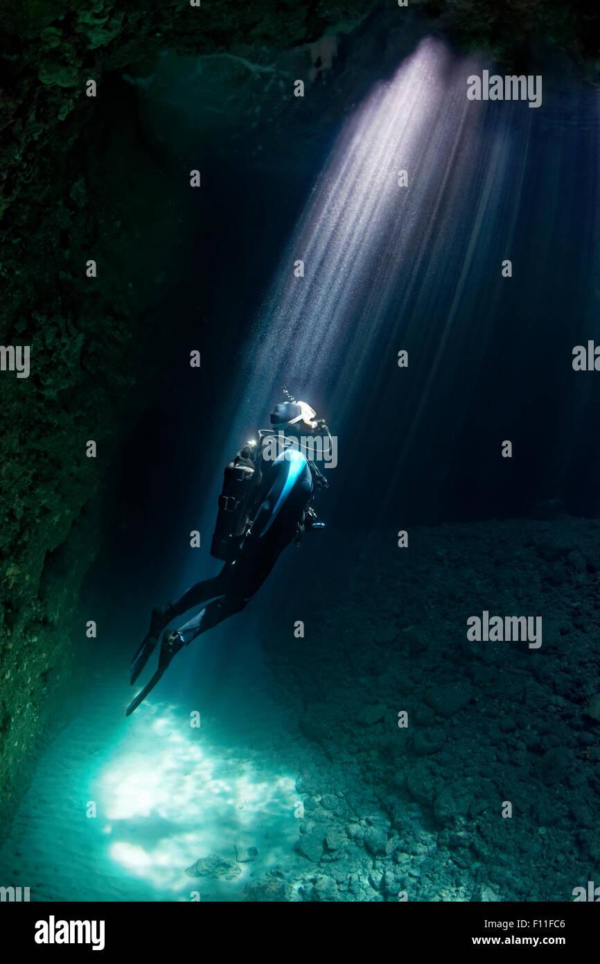 Diver in a cave, sun rays, island Corfu, Ionian Islands, Mediterranean Sea, Greece - Stock Image