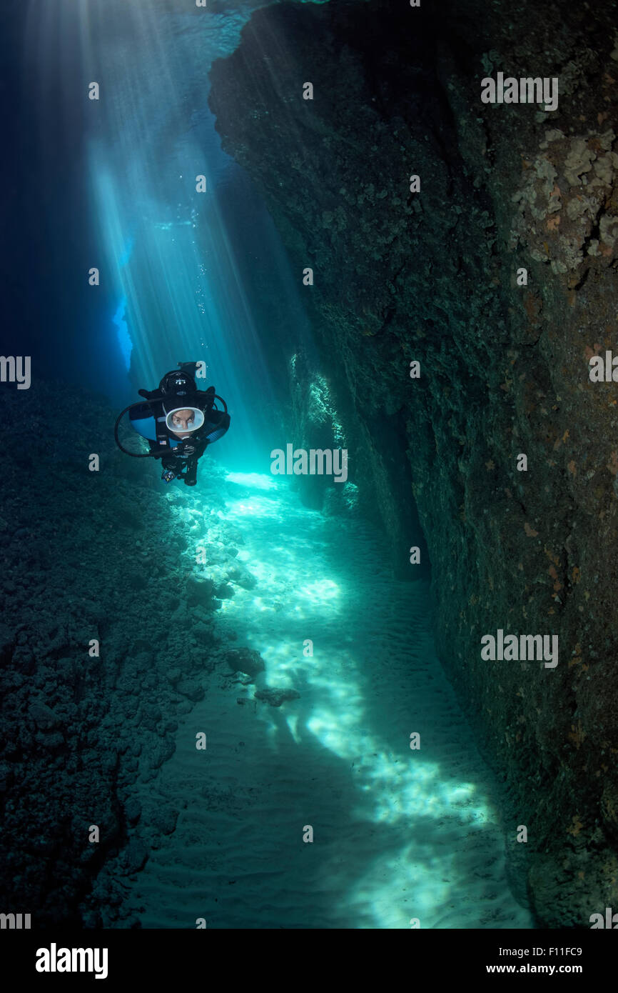 Diver in a narrow crevice with sun rays beaming down, island Corfu, Ionian Islands, Mediterranean Sea, Greece - Stock Image