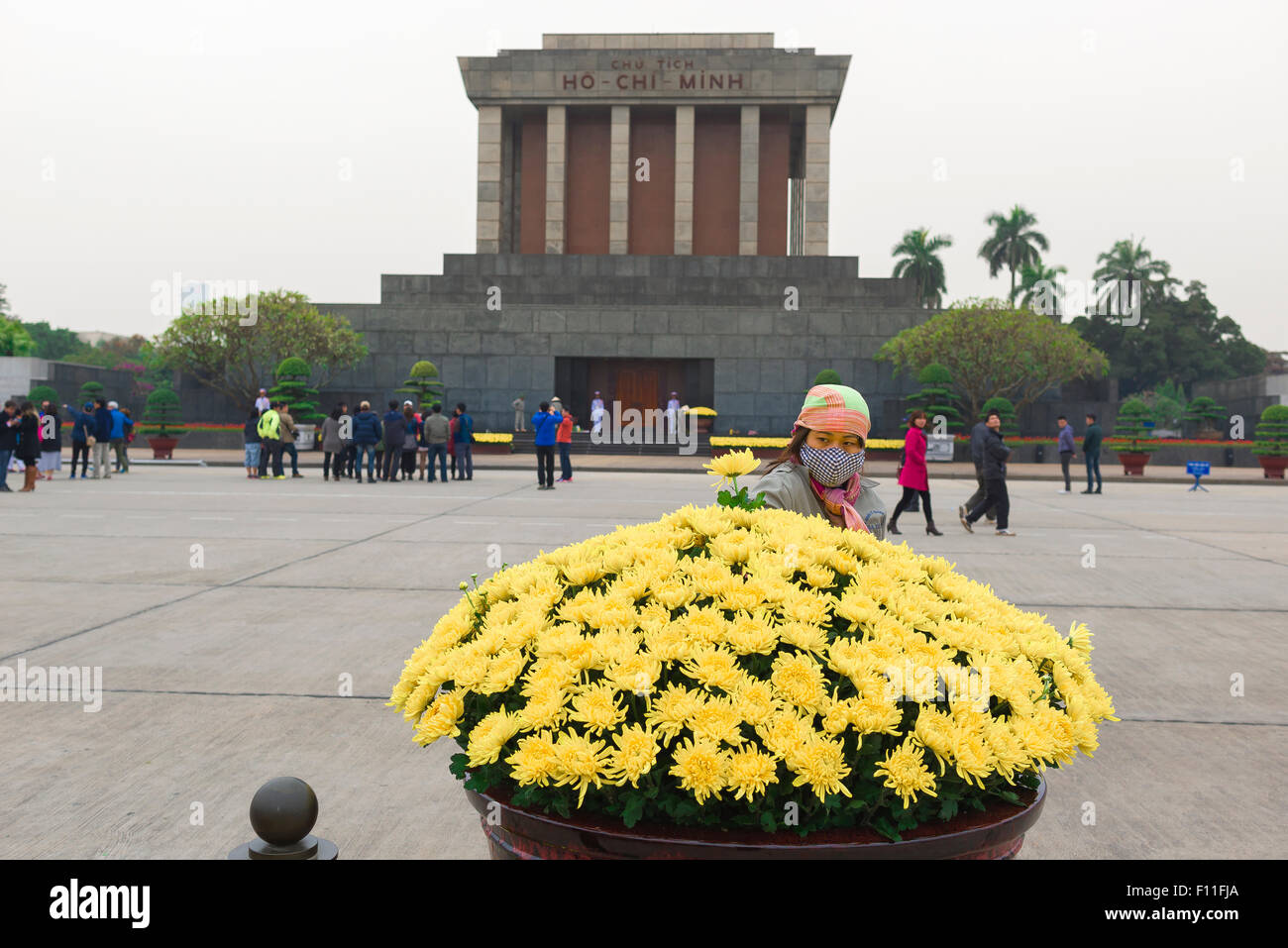 Ho Chi Minh mausoleum, a young Vietnamese worker plants the last flower in a large floral display at the site of - Stock Image
