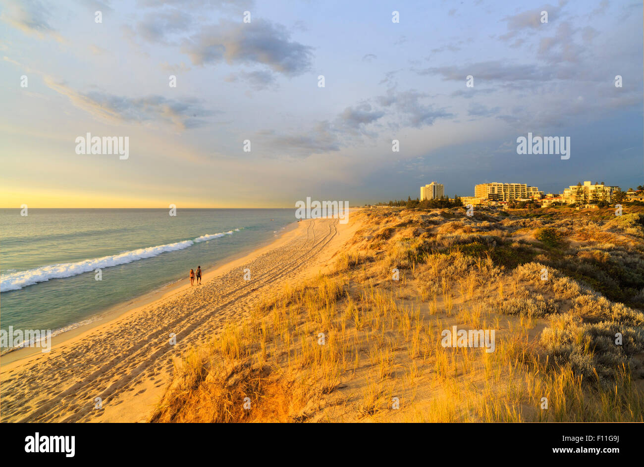 A couple walking along Scarborough Beach in the late afternoon summer sun. Perth, Western Australia - Stock Image