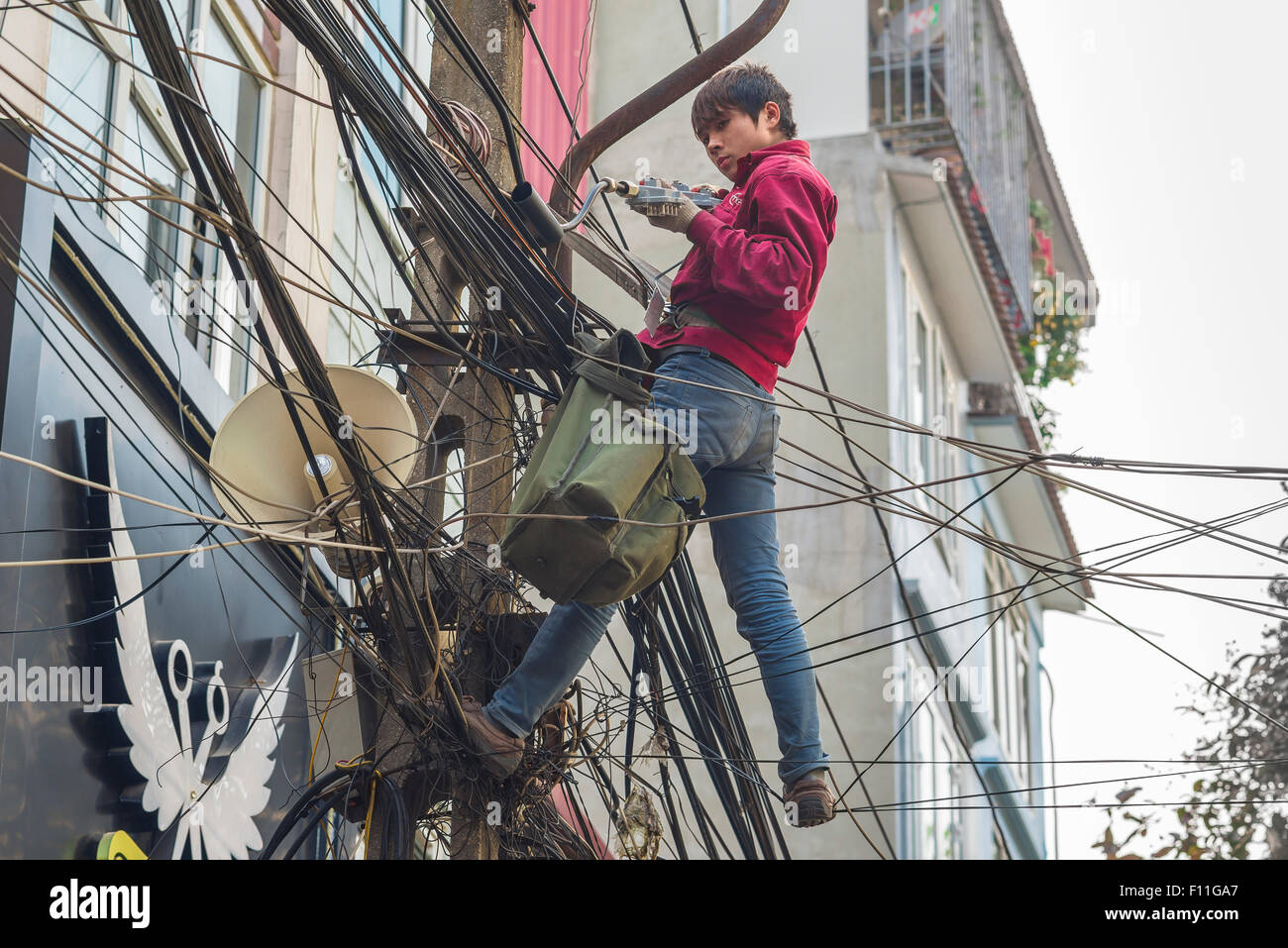 Vietnam street cables, above a street in the Old Quarter in Hanoi an electrical engineer works amid a dense tangle - Stock Image