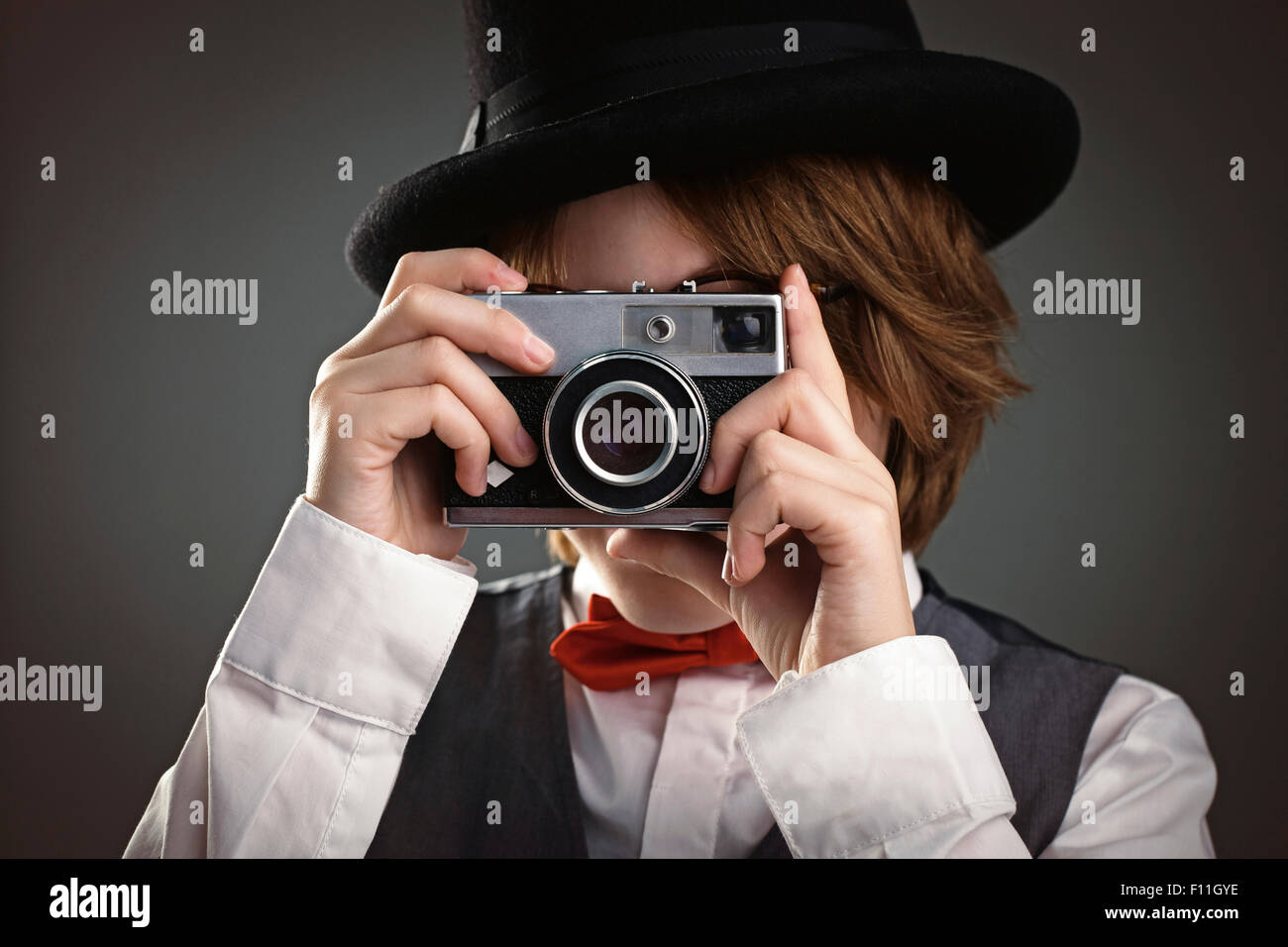 Close up of boy in top hat photographing with vintage camera Stock Photo
