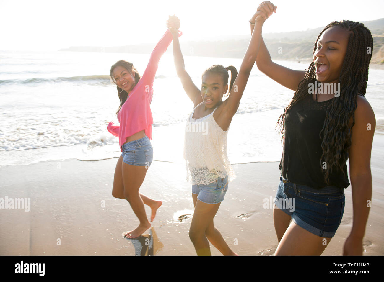 African American sisters holding hands on beach Stock Photo