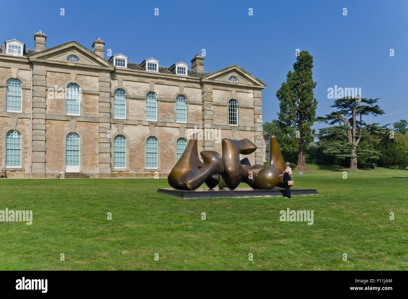 A woman examining The Three Piece Sculpture: Vertebrae by Henry Moore in the grounds of Compton Verney House - Stock Image