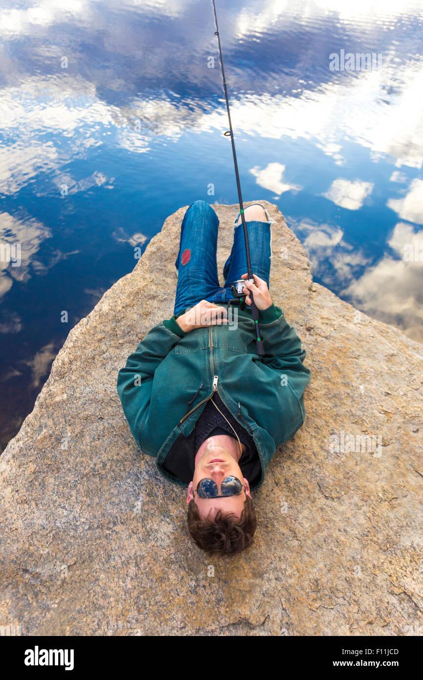 Caucasian man fishing in remote lake - Stock Image