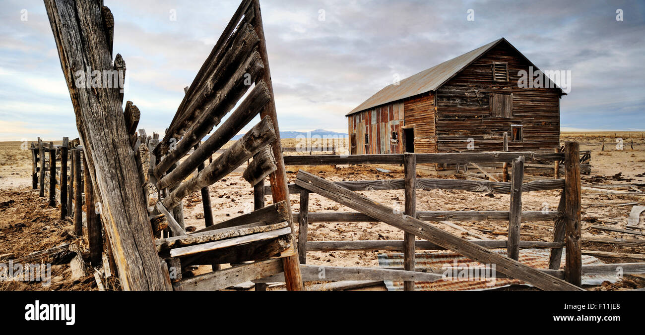 Close up of dilapidated fence and barn on abandoned farm - Stock Image