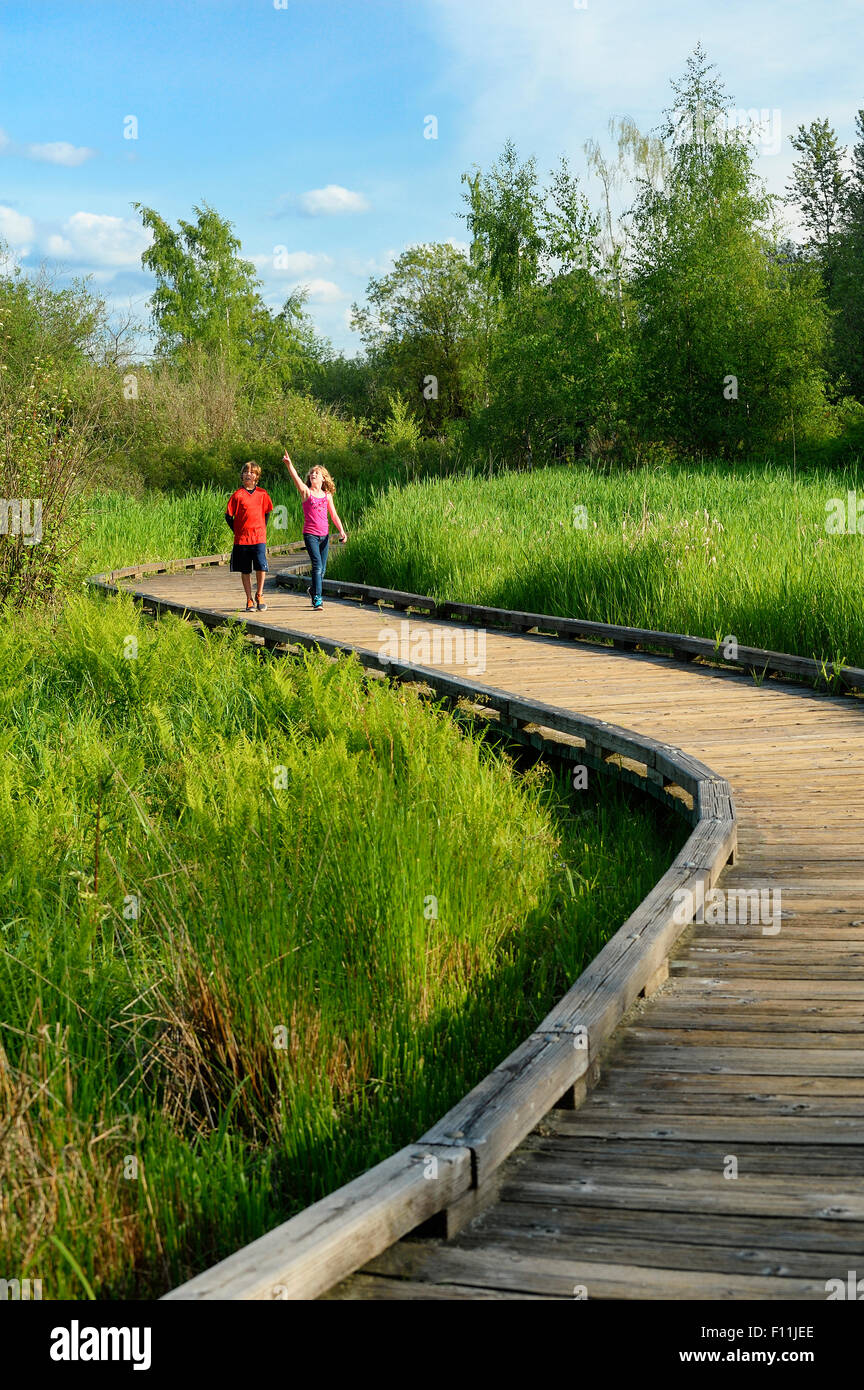 Children walking on wooden walkway in wetland marsh - Stock Image