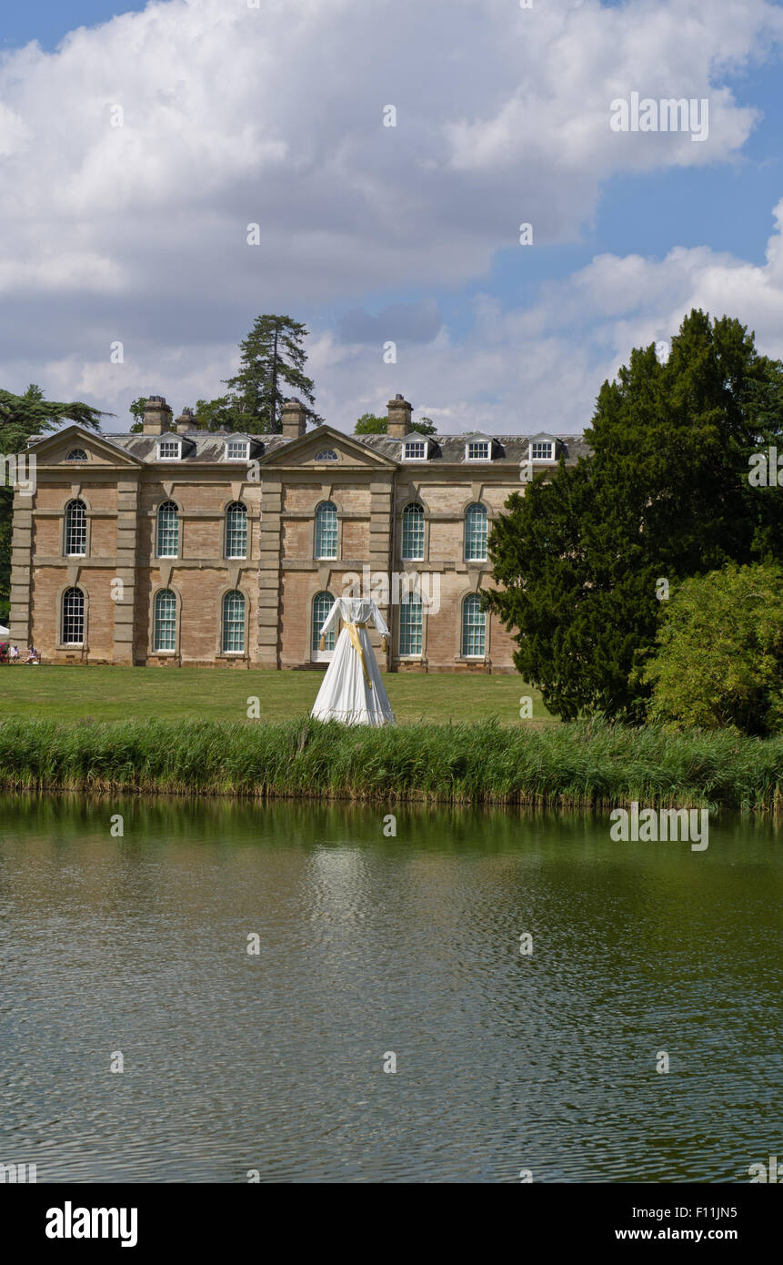 A view across the lake to Compton Verney House with the art installation, Kern Baby, centre stage. - Stock Image