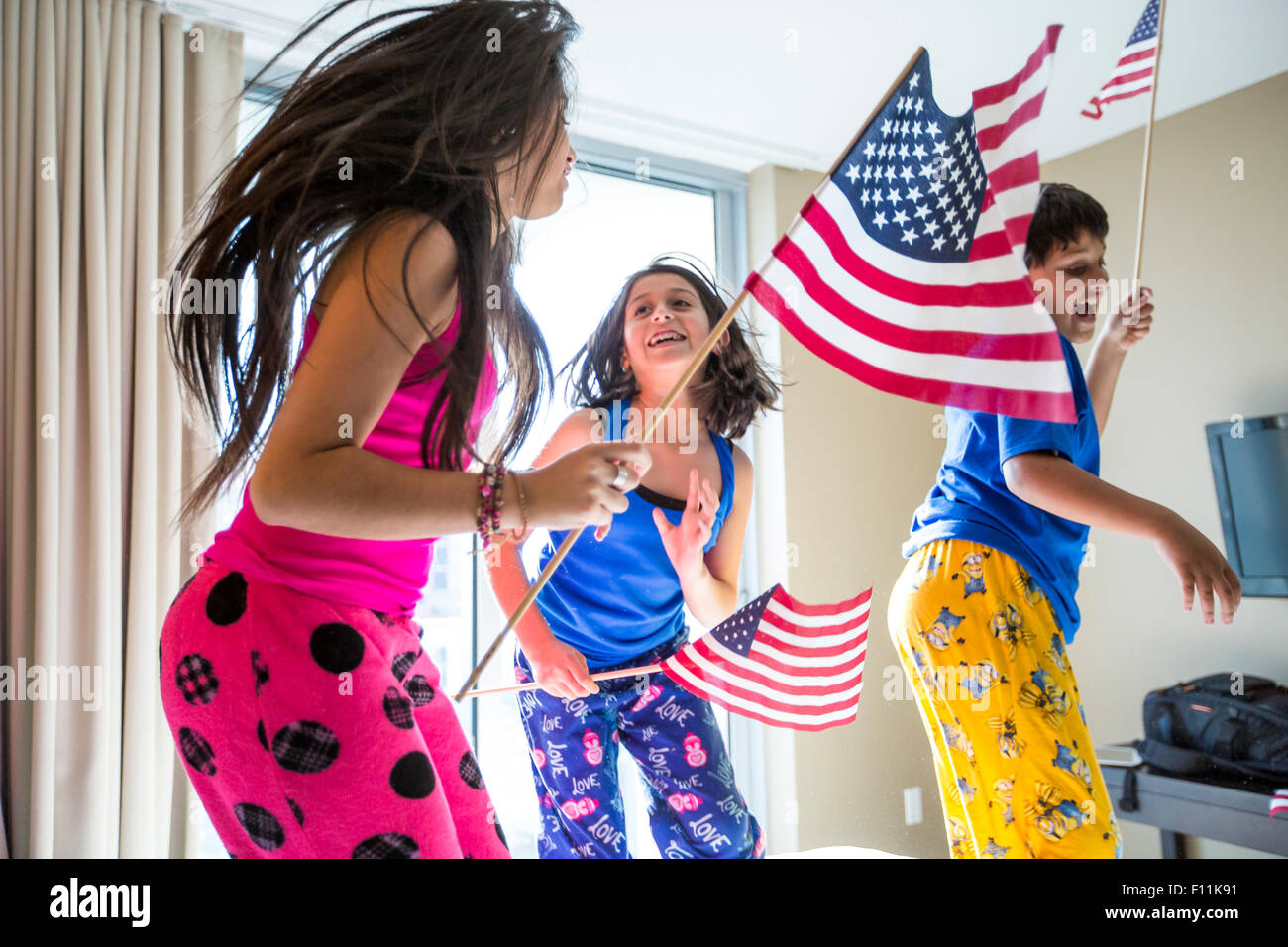 Hispanic children jumping with American flags Stock Photo