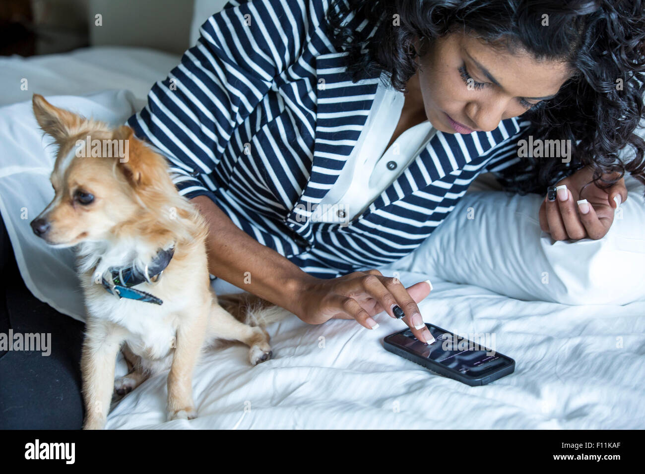 Mixed race woman using cell phone with dog on bed Stock Photo