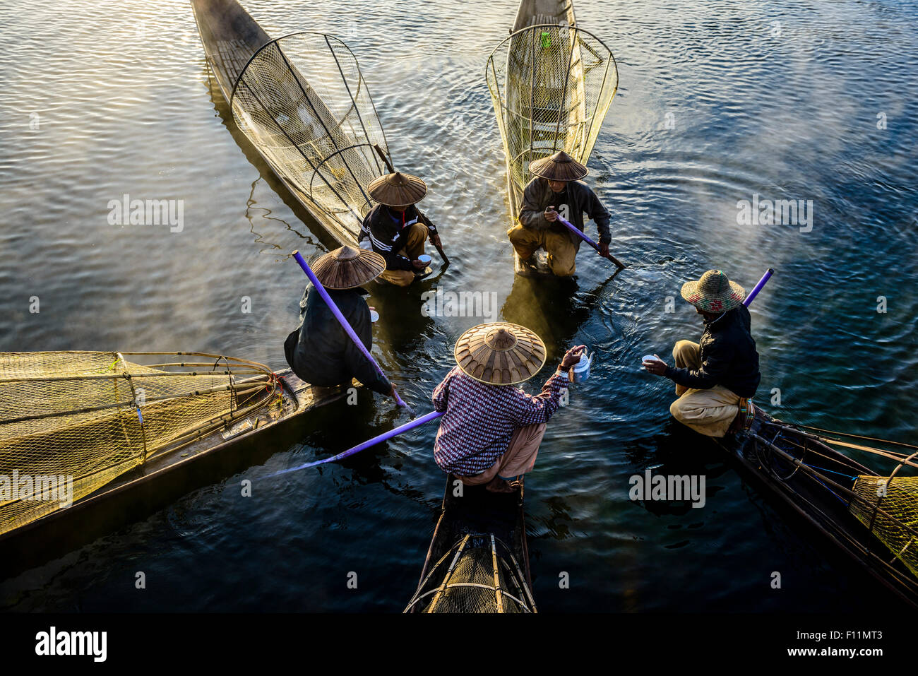 High angle view of Asian fishermen fishing in canoes on river - Stock Image