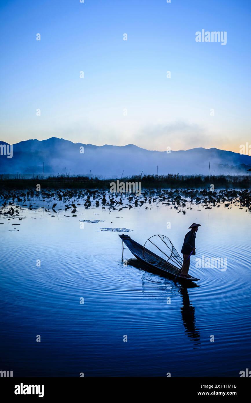Asian fisherman using fishing net in canoe on river - Stock Image