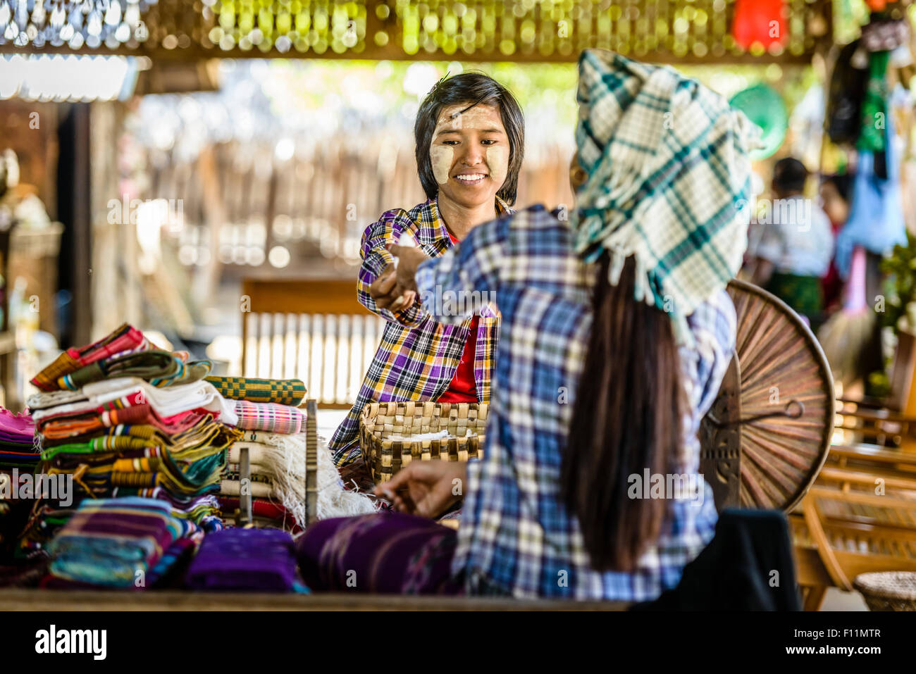 Asian teenage boy selling fabric at market - Stock Image