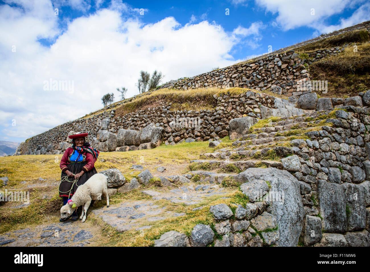 Older Hispanic woman walking llama on stone steps - Stock Image