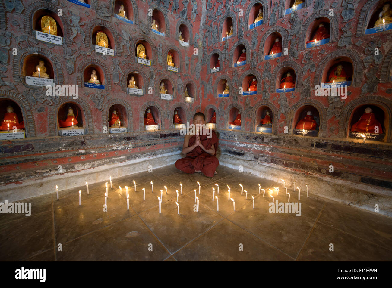 Asian monk-in-training praying in ancient temple - Stock Image