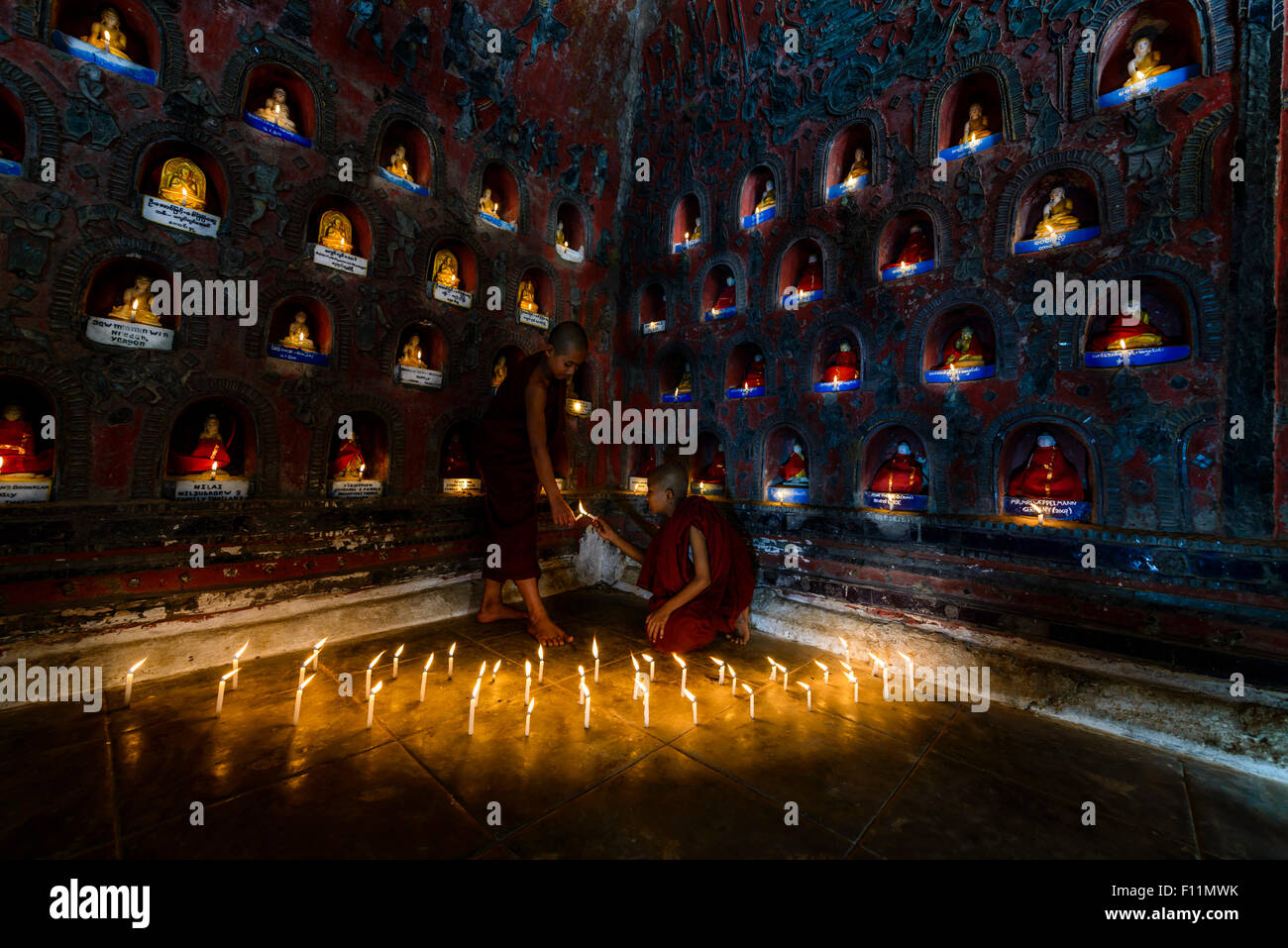 Asian monks-in-training lighting candles in ancient temple - Stock Image