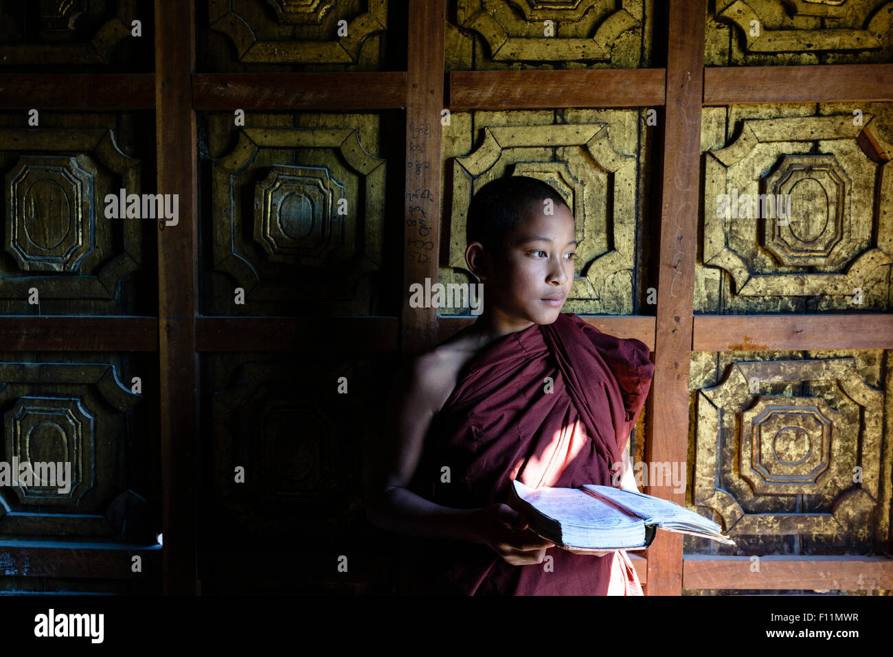Asian monk-in-training holding book in temple - Stock Image