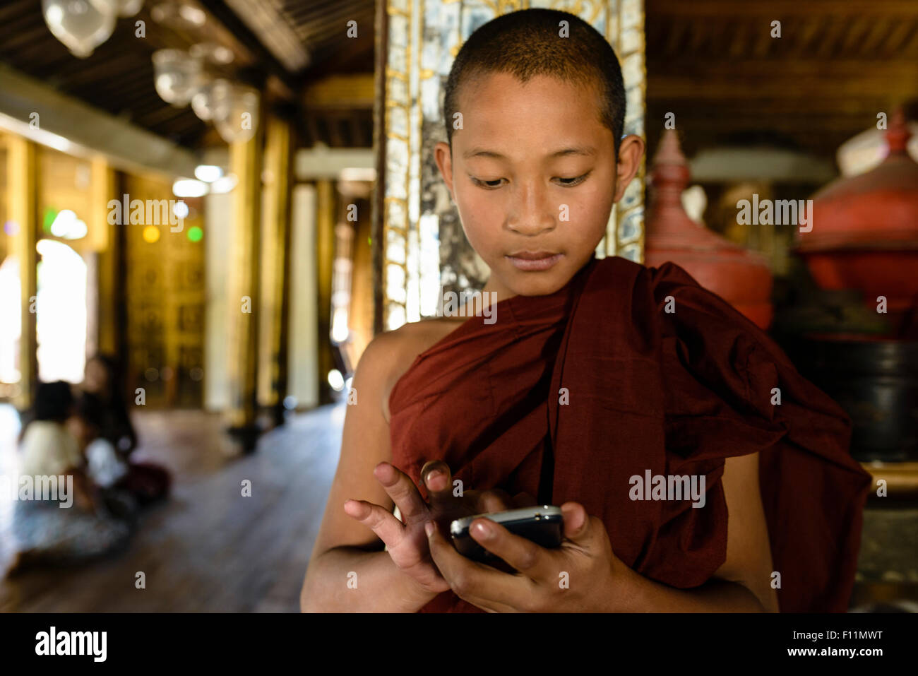 Asian monk-in-training using cell phone indoors - Stock Image