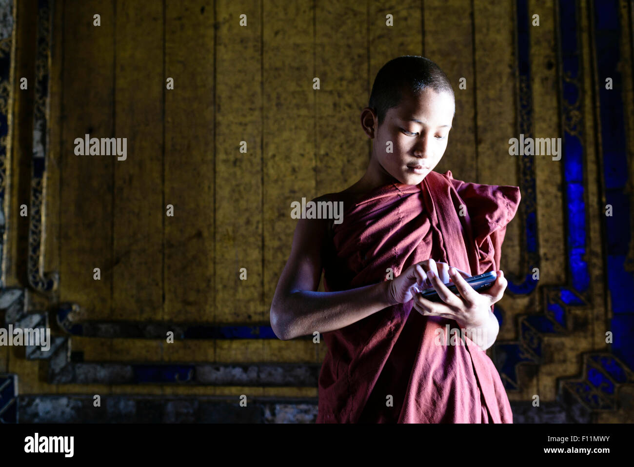 Asian monk-in-training using cell phone in temple - Stock Image