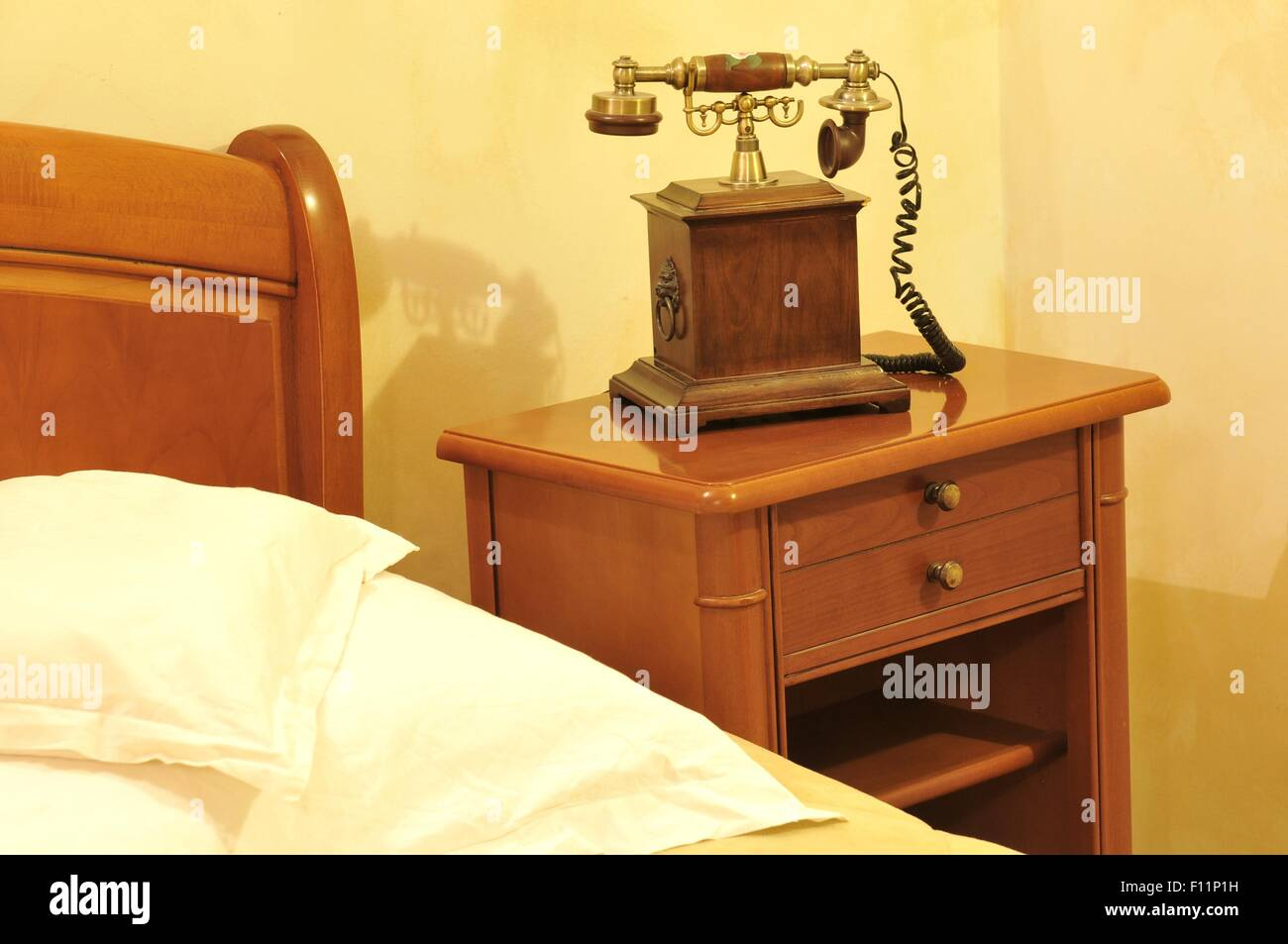 Detail of telephone by the bed in vintage bedroom - Stock Image