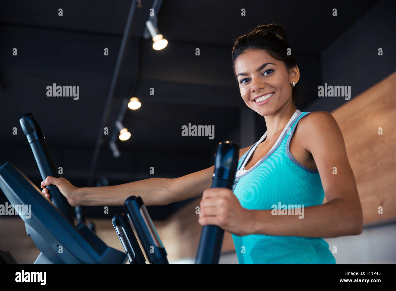 Smiling woman workout on exercises machine in fitness gym and looking at camera Stock Photo