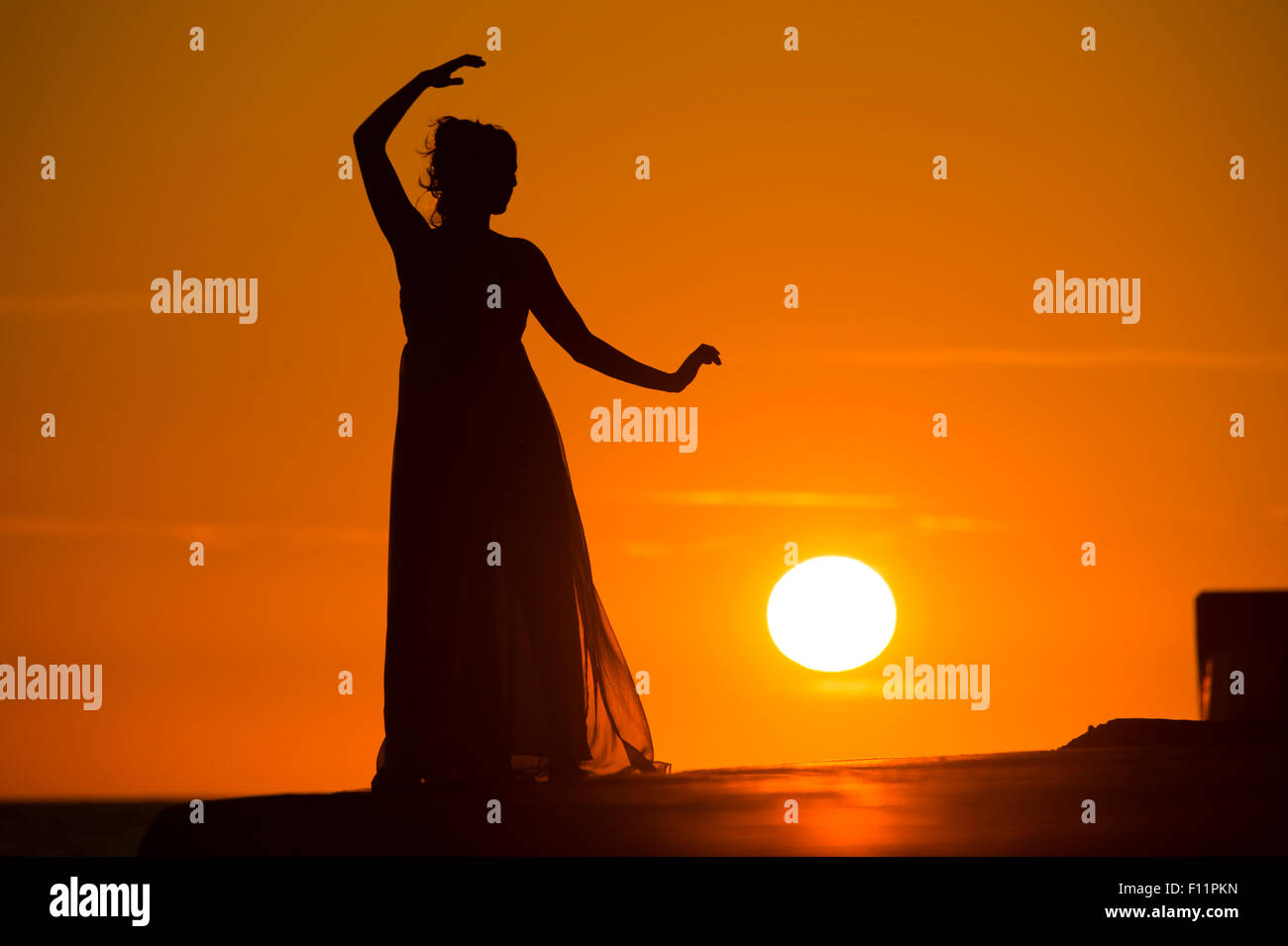 A silhouette of a women girl posing modeling as a 'greek goddess' at sunset - Stock Image
