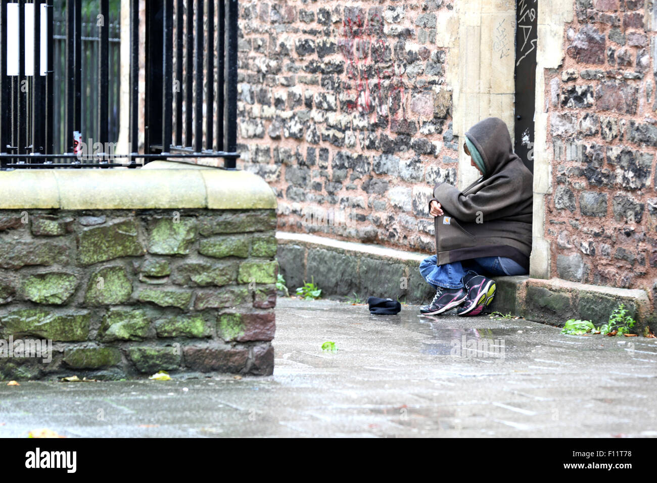 A female street beggar asking for money on a wet city street. Its a wet cold day and the female has wrapped herself - Stock Image