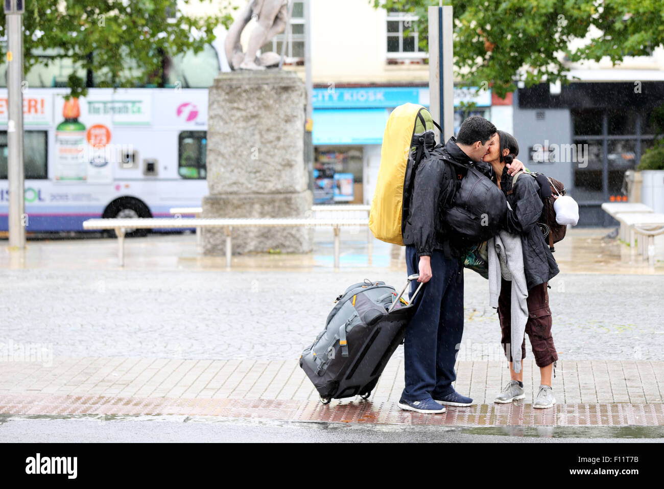 A couple kissing goodbye on a wet rainy afternoon in a busy city centre. Its pouring with rain but the male has - Stock Image