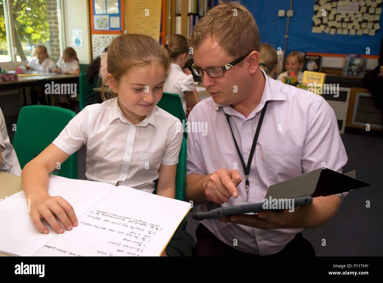 primary school teacher assisting pupil in classroom midlands uk