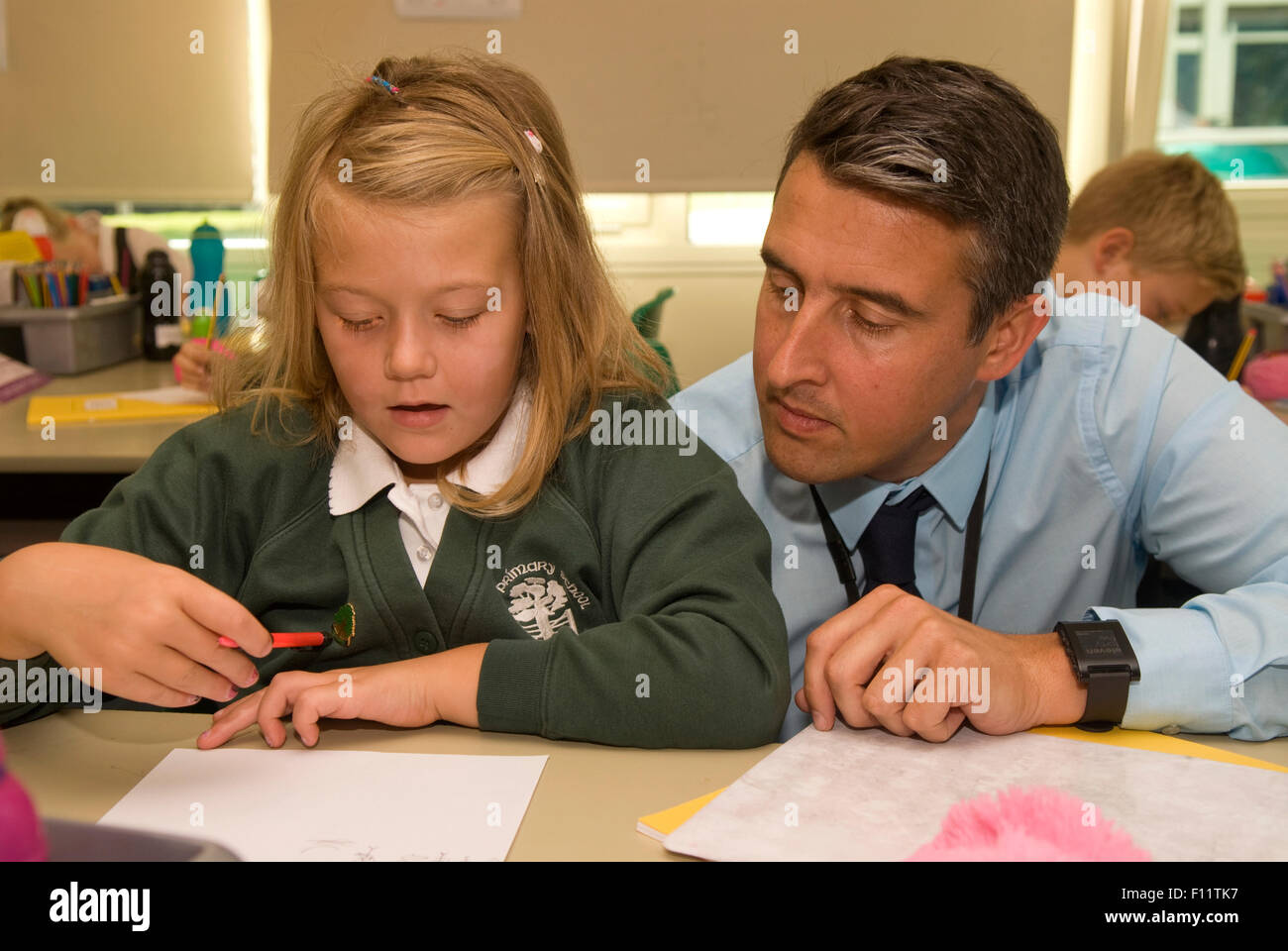 Primary school teacher assisting pupil in classroom, Midlands, UK. - Stock Image