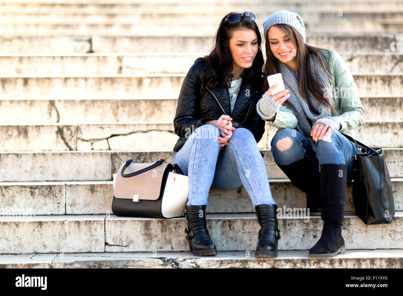 Two young and beautiful women sitting at the stairs and taking a selfie - Stock Image