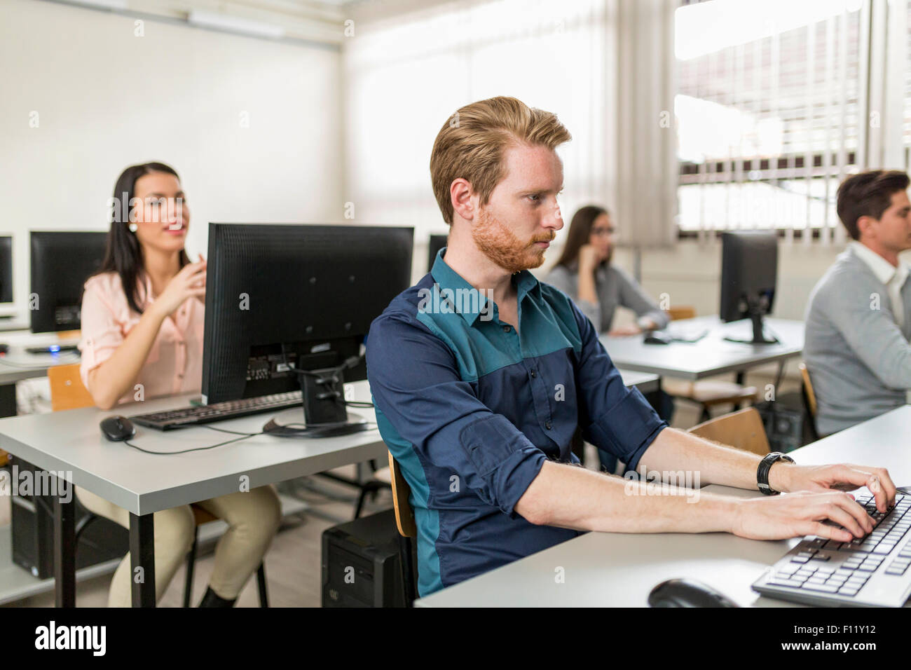 Young handsome student using computer in classroom - Stock Image
