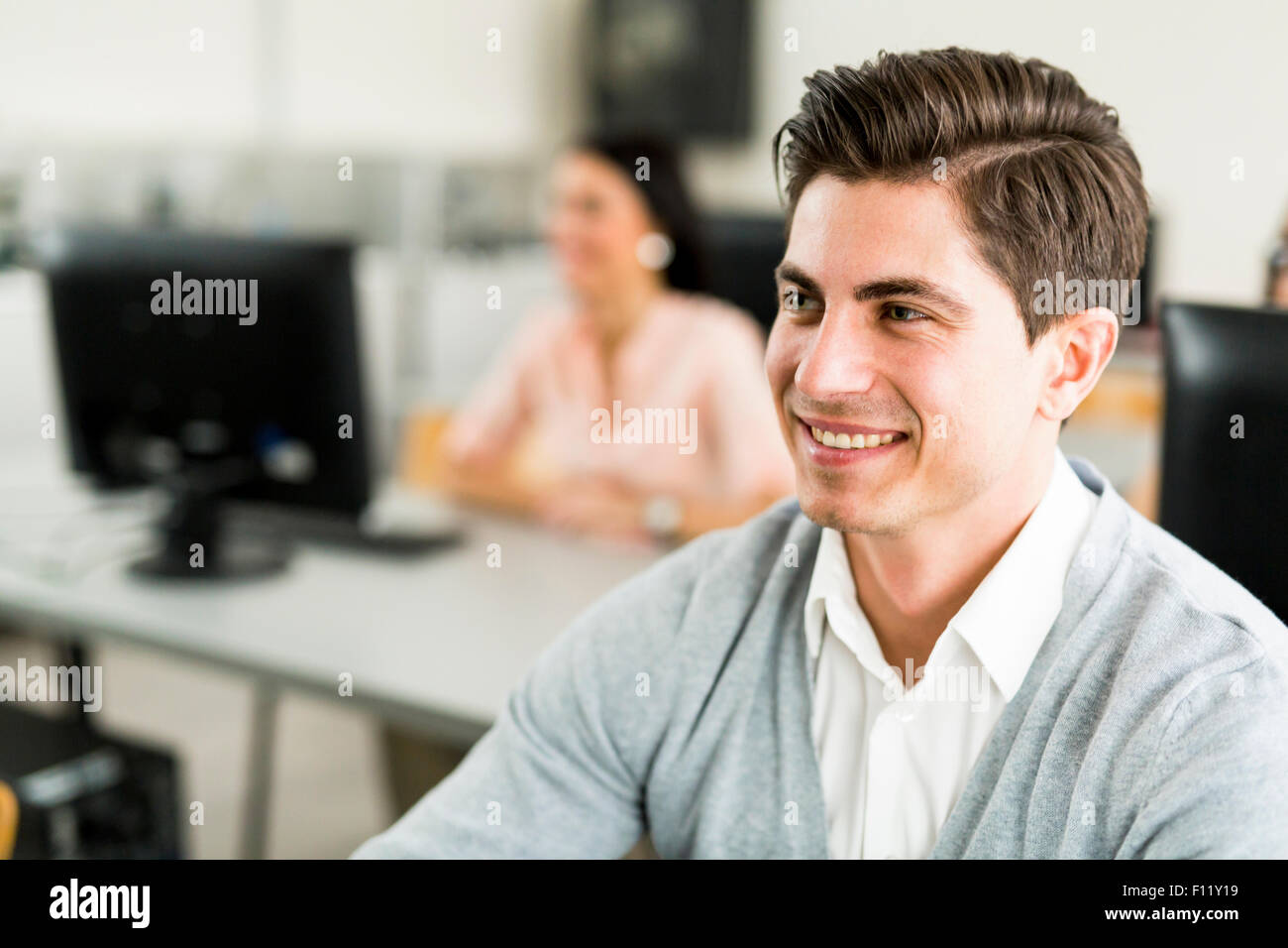 Young handsome man studying information technology in a classroom and smiling Stock Photo