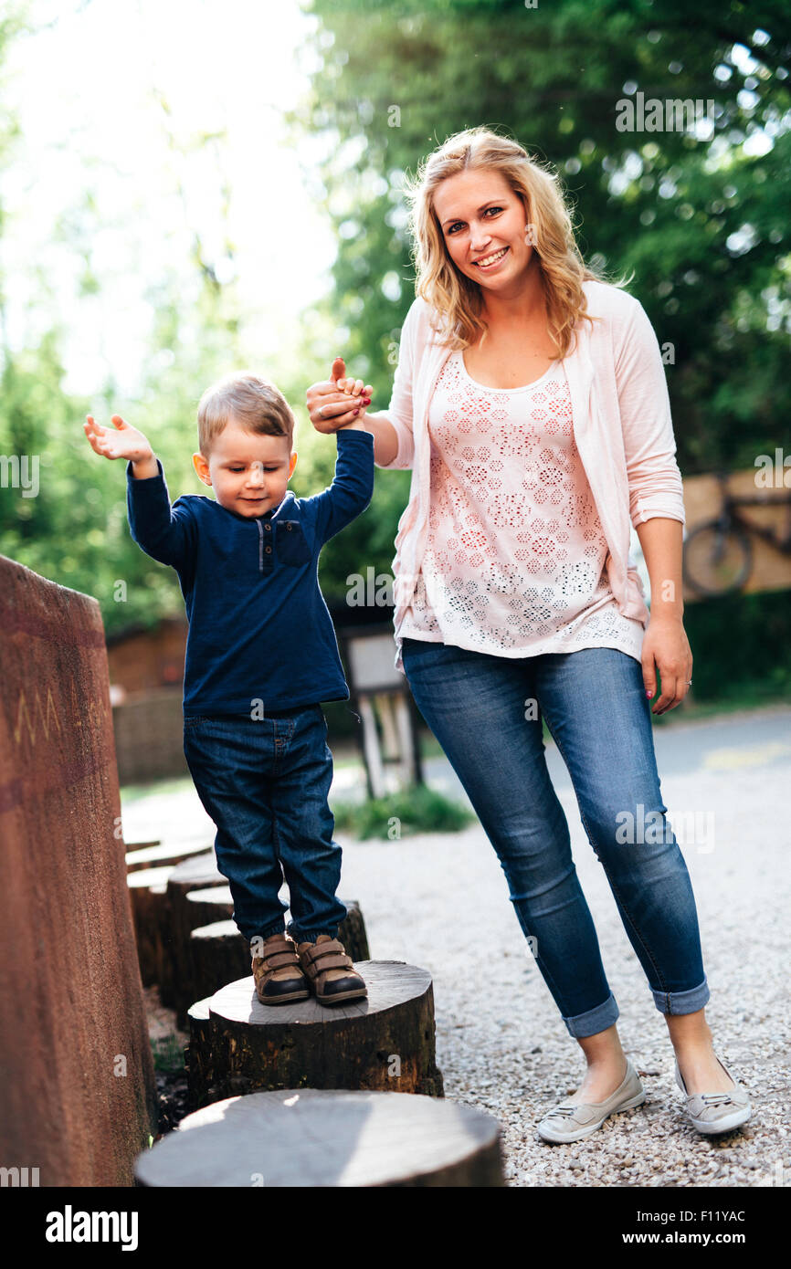 Beautiful young mother and her child holding hands outdoor - Stock Image