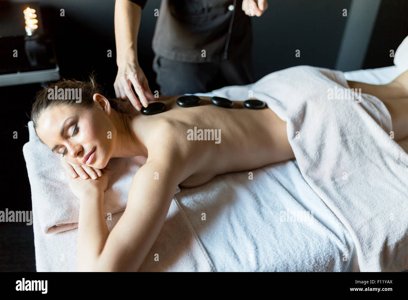 Masseur placing hot massage stones onto a young, beautiful lady's back - Stock Image