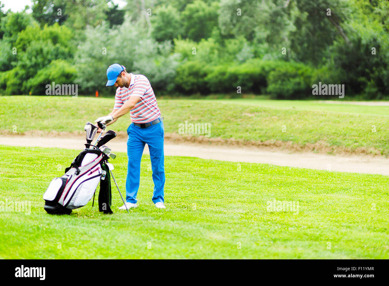 Golfer selecting appropriate club for the next shot - Stock Image