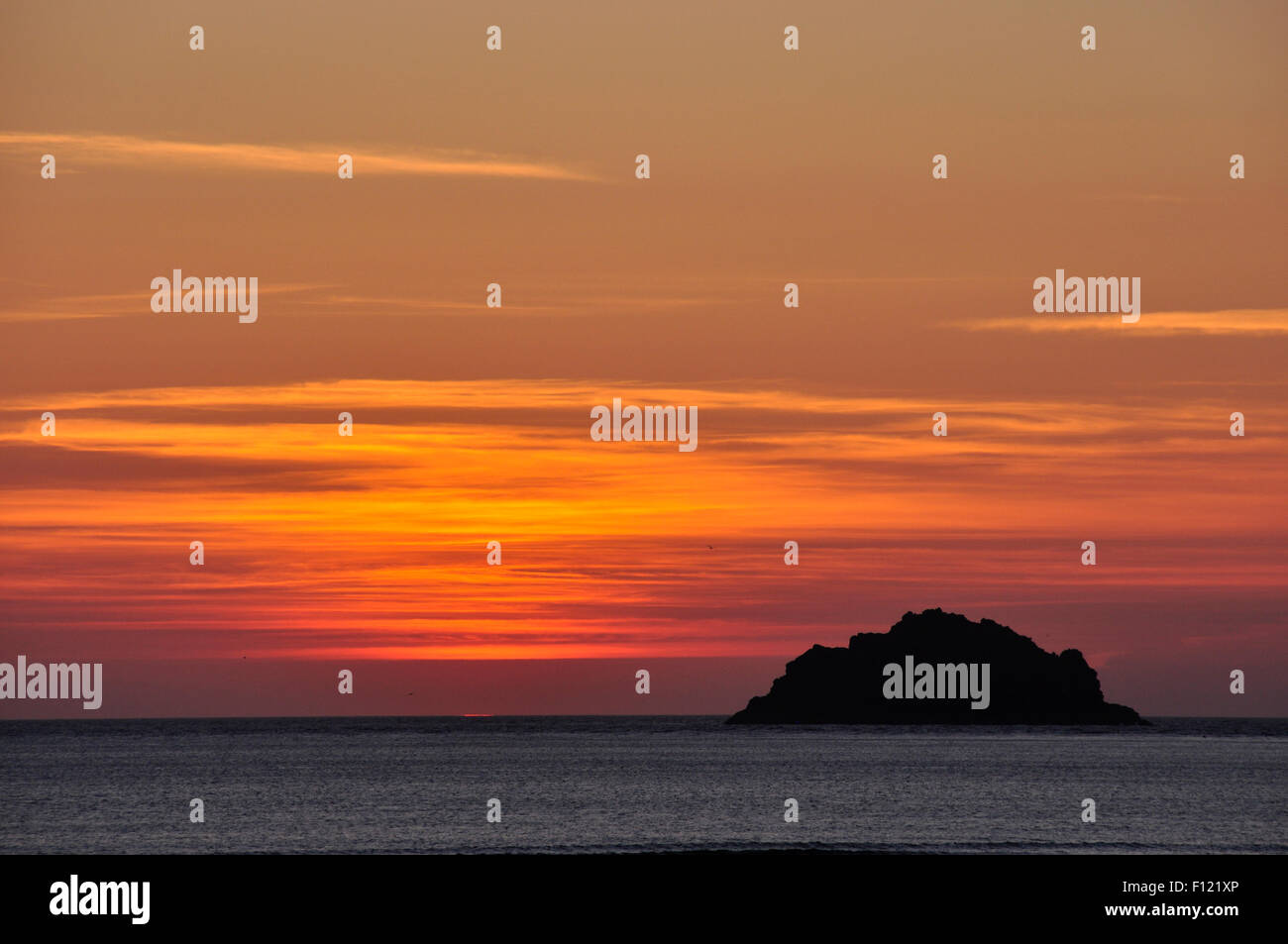 North Cornwall - orange red and gold skyscape - immediately after the sun has set over the sea - an island in black - Stock Image