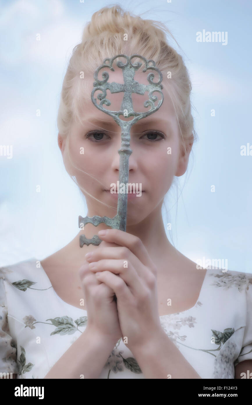 a woman is holding a big, old key in front of her face - Stock Image