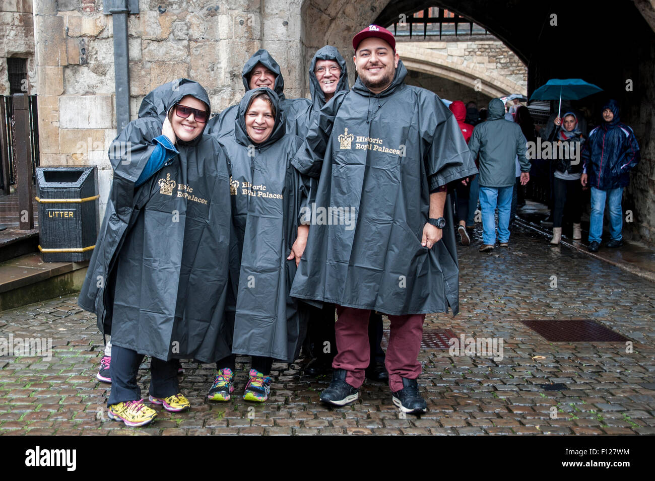 London, UK. 25 August 2015.  With the dry days of summer already a distant memory, tourists in matching ponchos - Stock Image