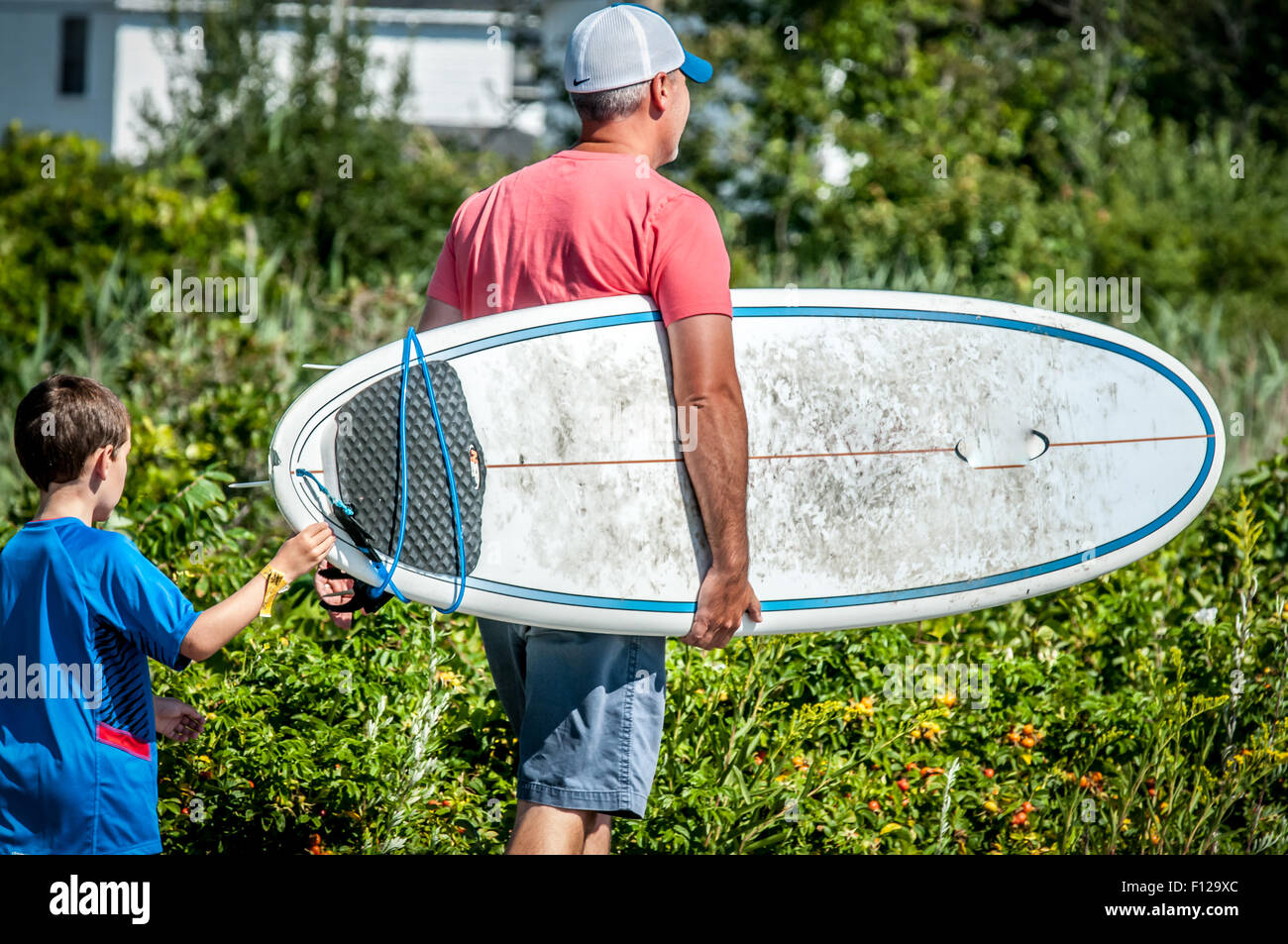 LOOKING FOR WAVES,On a nice Summer day this father, and son, walk down the town street with a surfboard, maybe looking - Stock Image