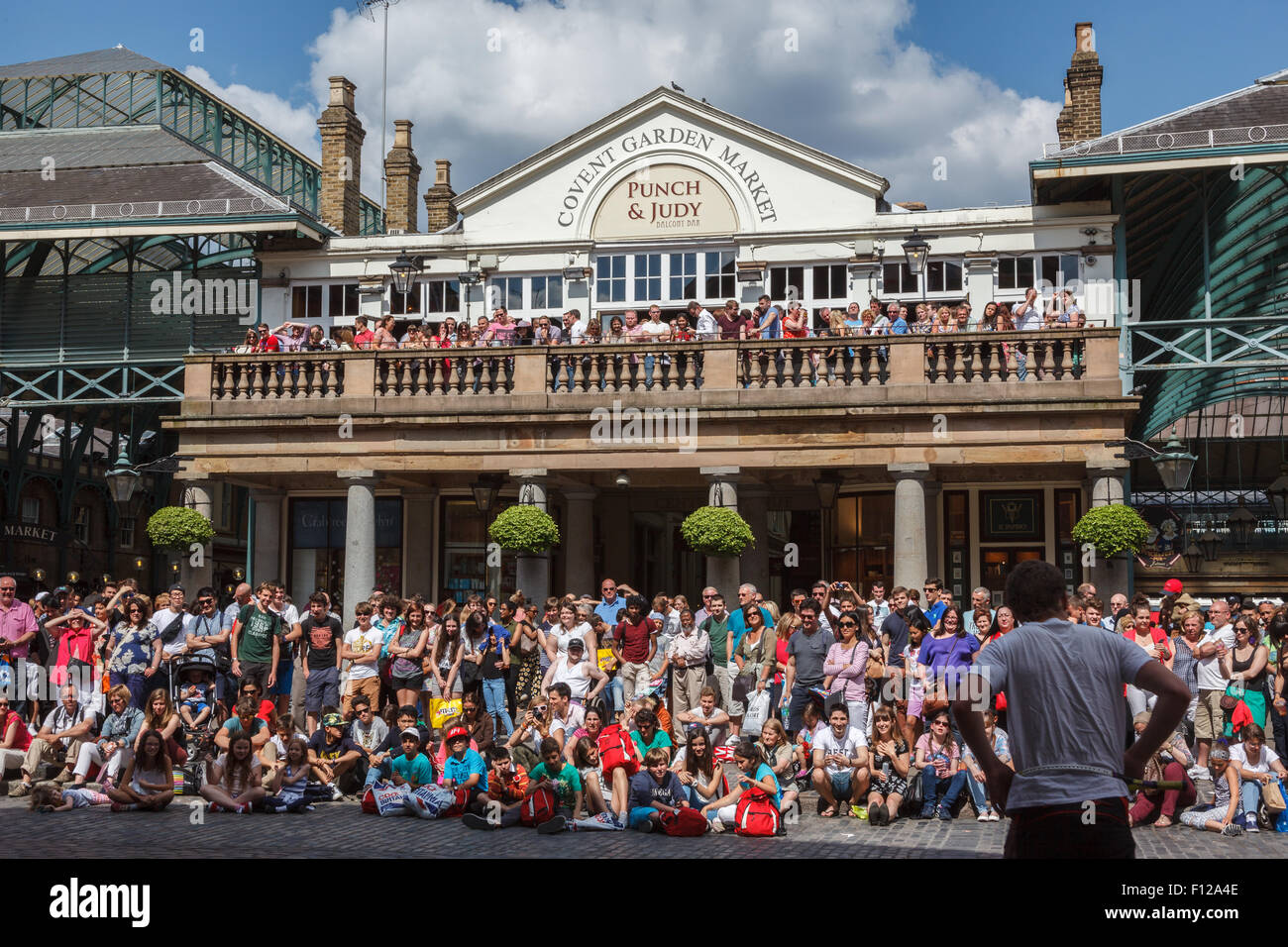 Street performer entertaining a crowd on a sunny day in London's Covent Garden piazza. Stock Photo