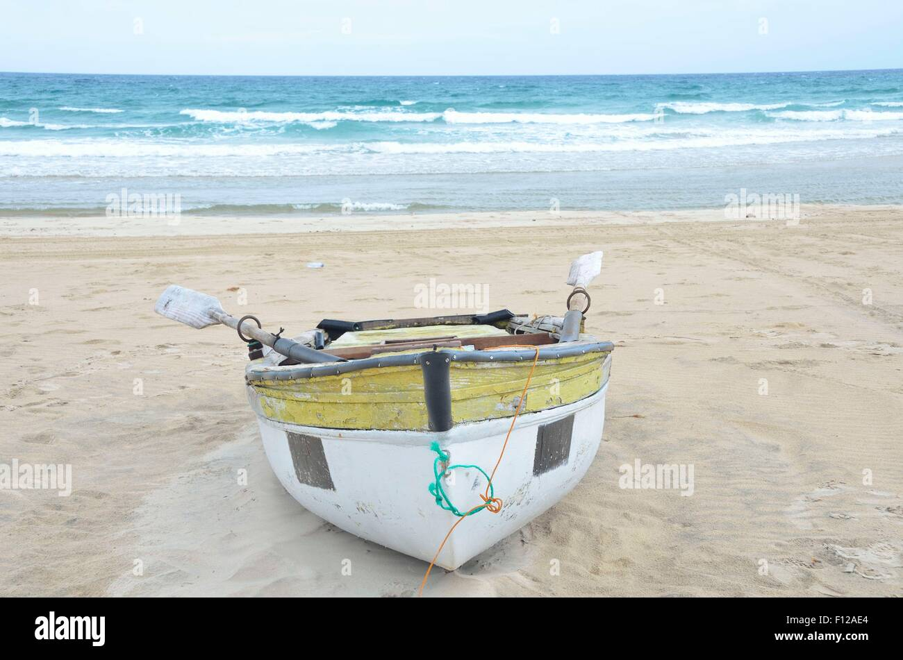This old, unsafe fishing boat lying on the beach at Inhambane, Mozambique is in daily use. - Stock Image