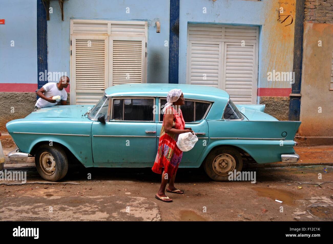 Blue vintage car parked on the pavement in a residential street in Havana, Cuba. A lady is walking by and a man - Stock Image