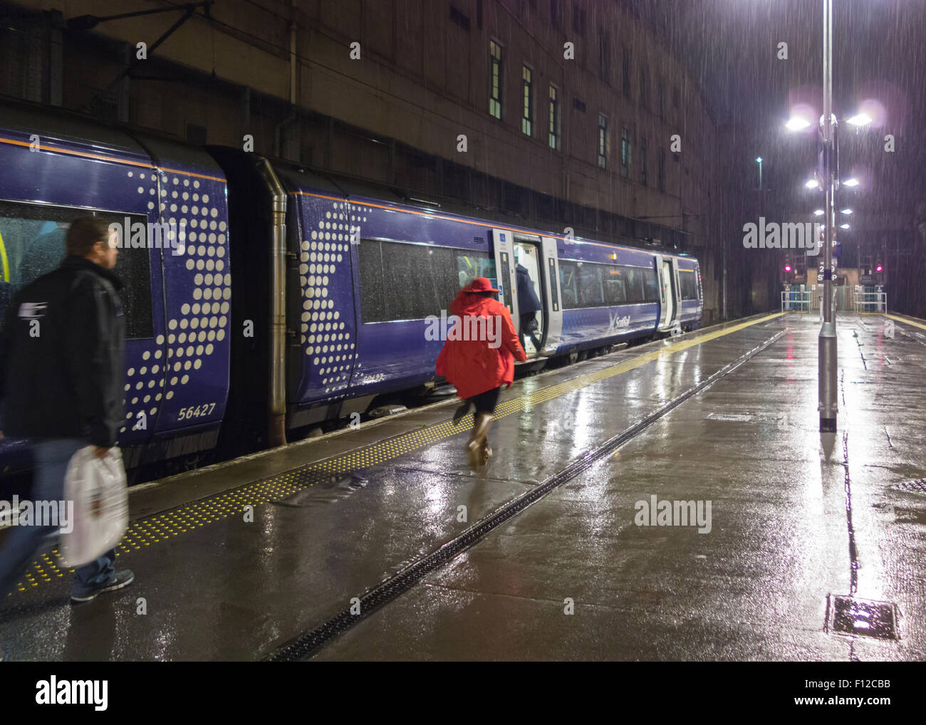 woman in red coat and hat running to catch train in the rain at night - Stock Image